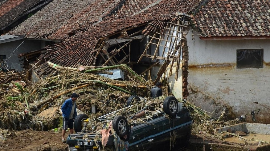 A man inspects a damaged vehicle in a village badly hit by a flash flood in Garut, West Java, Indonesia, Wednesday, Sept. 21, 2016. Torrential rains triggered floods and landslides on the main island of Java, killing a number villagers and forcing about 1,000 others to take shelter at military barracks or other temporary shelters, an official said Wednesday. (AP Photo)