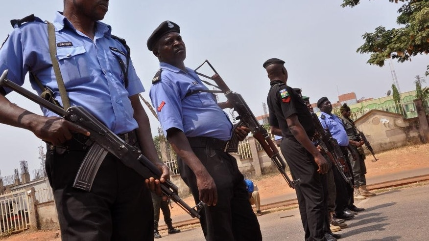 FILE- In this Saturday Feb. 7, 2015 file photo Nigeria police officers block a road in the city of Abuja, Nigeria. An elite Nigerian police squad set up to combat violent crime is torturing detainees to extract lucrative bribes and confessions, Amnesty International said in a report published, Wednesday Sept. 21, 2016 The report says the Special Anti-Robbery Squad demands bribes, steals and extorts money from criminal suspects and their families. (AP Photo/Olamikan Gbemiga, File)