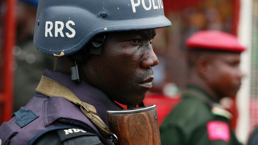 FILE- In this Thursday, May. 1, 2014 file photo, a police officer stand guards during a demonstration in Lagos, Nigeria. An elite Nigerian police squad set up to combat violent crime is torturing detainees to extract lucrative bribes and confessions, Amnesty International said in a report published Wednesday Sept. 21, 2016. The report says the Special Anti-Robbery Squad demands bribes, steals and extorts money from criminal suspects and their families. ( AP Photo/Sunday Alamba, File)