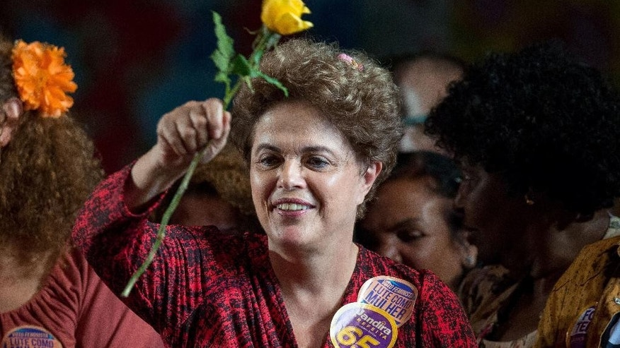 Former President Dilma Rousseff holds a flower during a rally for Rio de Janeiro mayoral candidate Jandira Feghali in Rio de Janeiro, Brazil, Wednesday, Sept. 21, 2016. Rousseff spoke in support of her mentor, Luiz Inacio Lula da Silva, a day after a federal judge ruled that he must stand trial on corruption and money-laundering charges. A conviction could ruin Lula's chances of running for president again in 2018 and returning the leftist Workers' Party to power. (AP Photo/Mauro Pimentel)