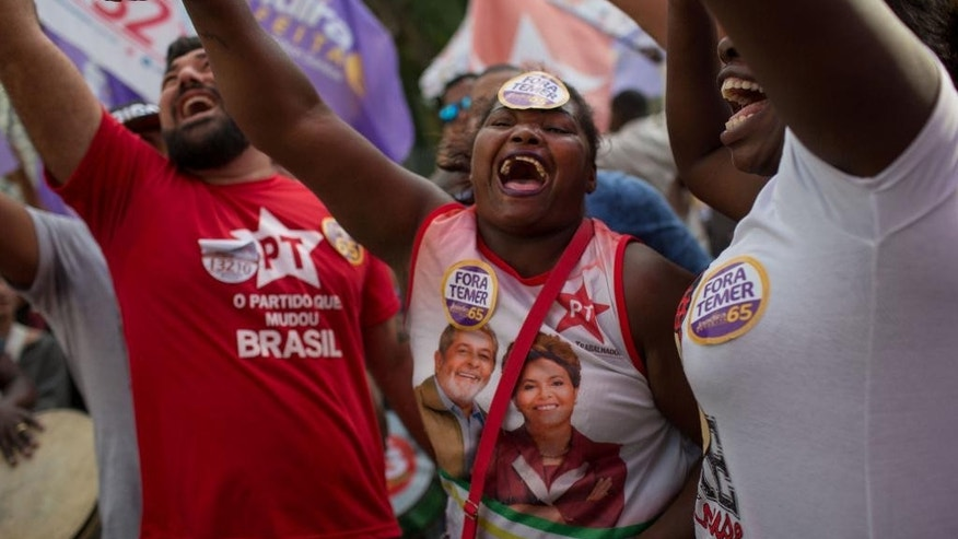 Supporters of former President Dilma Rousseff cheer during a rally for Rio de Janeiro mayoral candidate Jandira Feghali in Rio de Janeiro, Brazil, Wednesday, Sept. 21, 2016. Rousseff spoke in support of her mentor, Luiz Inacio Lula da Silva, a day after a federal judge ruled that he must stand trial on corruption and money-laundering charges, possibly thwarting the political comeback of one of the remaining dominant forces of Latin America's left. (AP Photo/Mauro Pimentel)