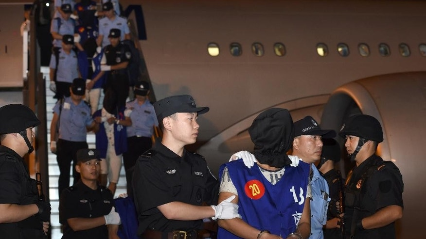 In this photo released by China's Xinhua News Agency, hooded internet fraud suspects are escorted off a plane by Chinese police at Lukou International Airport in Nanjing in eastern China's Jiangsu Province after being deported from Cambodia, Tuesday, Sept. 20, 2016. Cambodia has deported 13 Taiwanese and 50 Chinese suspects to China, a senior police official said Wednesday. (Han Yuqing/Xinhua via AP)