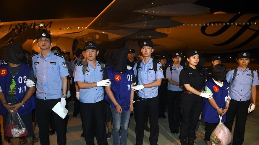 In this Sept. 20, 2016 photo released by China's Xinhua News Agency, Chinese police stand with hooded internet fraud suspects after they were escorted off a plane at Lukou International Airport in Nanjing in eastern China's Jiangsu Province after being deported from Cambodia. Cambodia has deported 13 Taiwanese and 50 Chinese suspects to China, a senior police official said Wednesday. (Han Yuqing/Xinhua via AP)