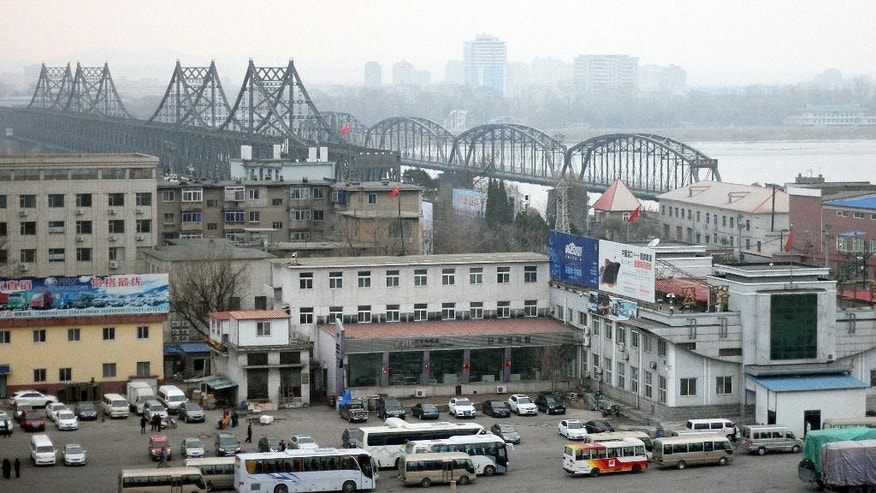 In this Thursday, March 17, 2016 photo, vehicles wait at a border checkpoint to cross into North Korea in Dandong in northeastern China's Liaoning Province. Chinese authorities are investigating a company that researchers say sold North Korea materials that can be used by its growing nuclear weapons program in a crackdown that reflects Beijing's growing frustration with its isolated neighbor. (Chinatopix via AP)