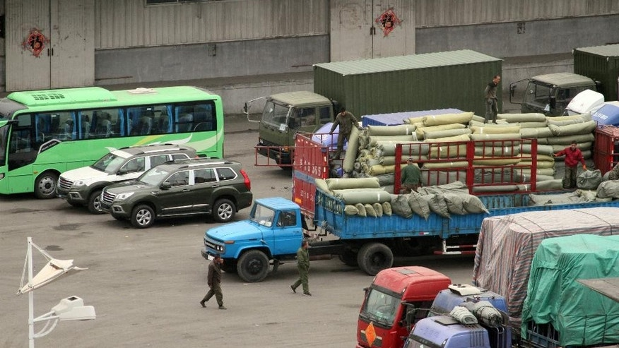 In this Thursday, March 17, 2016 photo, cargo trucks and other vehicles wait at a border checkpoint to cross into North Korea in Dandong in northeastern China's Liaoning Province. Chinese authorities are investigating a company that researchers say sold North Korea materials that can be used by its growing nuclear weapons program in a crackdown that reflects Beijing's growing frustration with its isolated neighbor. (Chinatopix via AP)