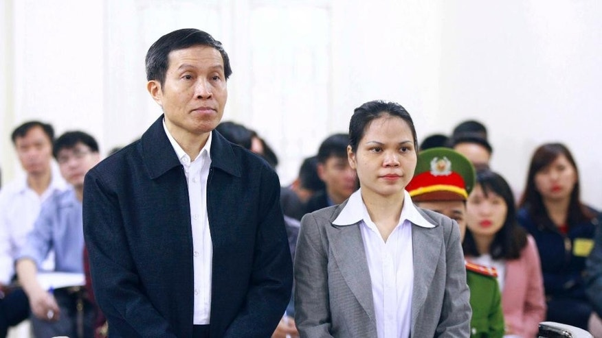 FILE - In this March 23, 2016 file photo, Vietnam's prominent blogger Nguyen Huu Vinh, left, and his assistant Nguyen Thi Minh Thuy stand together during a trial in Hanoi, Vietnam. A court in Hanoi began hearing an appeal Thursday, Sept. 22, 2016, from a prominent Vietnamese blogger who was sentenced earlier this year to five years in prison for anti-state writings. (Bui Doan Tan/Vietnam News Agency via AP, File)