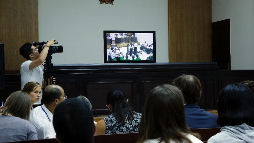 Media and diplomats watch a live screen showing prominent blogger Nguyen Huu Vinh, right, and his colleague Nguyen Thi Minh Thuy, left, in an appeals court in Hanoi, Vietnam, Thursday, Sept. 22, 2016. Vinh who was sentenced to five years in prison earlier this year for anti-state writings and Thuy who received three years behind bars on the same charge, appeal their sentences. (AP Photo/Tran Van Minh)