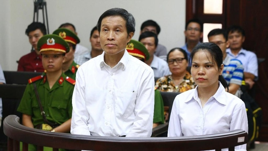 Vietnamese prominent blogger Nguyen Huu Vinh, left, and his colleague Nguyen Thi Minh Thuy stand at the dock during their trial at the Higher People's Court in Hanoi, Vietnam, Thursday, Sept. 22, 2016. The court heard appeals from the prominent blogger who was sentenced to five years in prison for anti-state writings. Nguyen Huu Vinh, better known as Anh Ba Sam, was convicted of abusing democratic freedoms to infringe on the interests of the state and sentenced to five years in prison in March. (Doan Tan/Vietnam News Agency via AP)