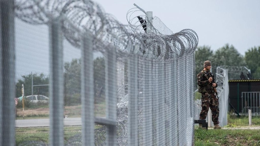 A Hungarian soldier patrols at the transit zone at Hungary's southern border with Serbia near Tompa, 169 km southeast of Budapest, Hungary, Wednesday, Sept. 21, 2016. Hungarian prison inmates have ramped up their production of razor wire, working around the clock as Hungary prepares to build a second fence on the border with Serbia to keep out refugees and other migrants. (Sandor Ujvari/MTI via AP)