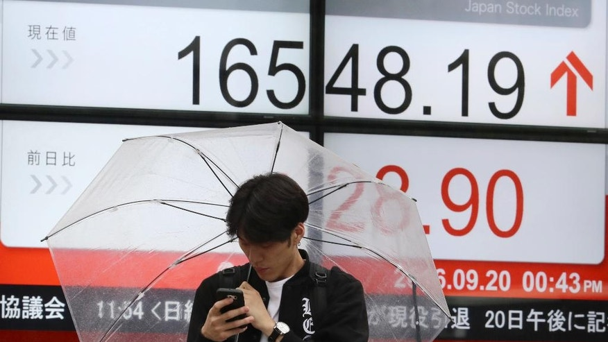 FILE - In this Tuesday, Sept. 20, 2016 file photo, a man stands near an electronic stock board showing Japan's Nikkei 225 index at a securities firm in Tokyo. Japan's trade balance slipped into deficit in August, for the first time in three months, as a stronger yen sapped exports, the Finance Ministry reported Wednesday, Sept. 21. (AP Photo/Eugene Hoshiko, File)