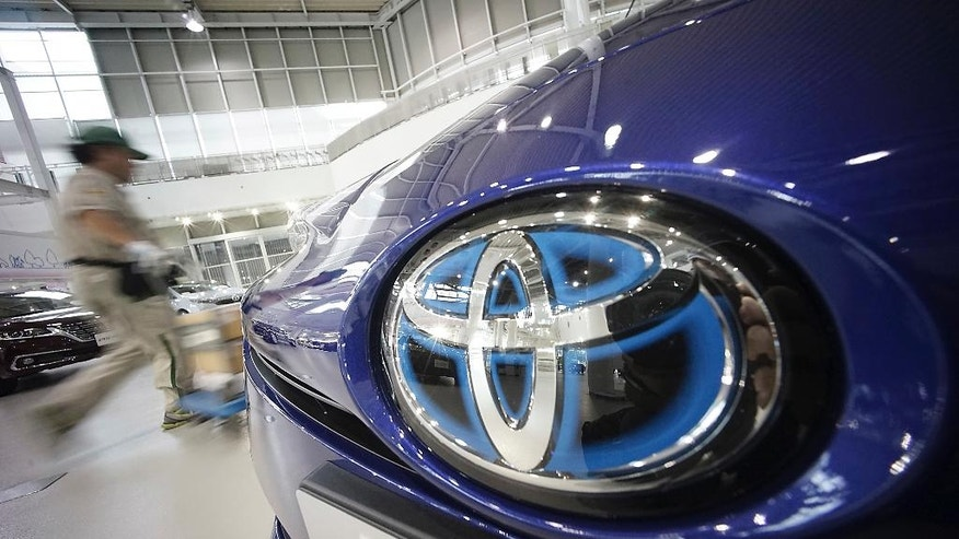 FILE - In this June 29, 2016 file photo, a delivery man pushes a cart past a Toyota car at a Toyota showroom in Tokyo. Japan's trade balance slipped into deficit in August, for the first time in three months, as a stronger yen sapped exports, the Finance Ministry reported Wednesday, Sept. 21. Japan's car exports fell 9.4 percent while exports of machinery, chemicals and electronic devices also dropped. But imports also weakened, with purchases of oil, gas and other fuels falling nearly 35 percent. (AP Photo/Eugene Hoshiko, File)