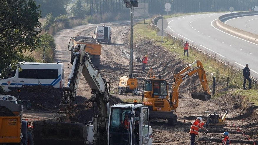 @Workers begin construction of a 4-meter- (13-foot) high wall along the roadway leading to the Calais port, outside Calais, northern France, Wednesday, Sept. 21, 2016. The kilometer-long wall being paid for by Britain, is a new barrier to try to keep migrants from crossing the English Channel. (AP Photo/Michel Spingler)