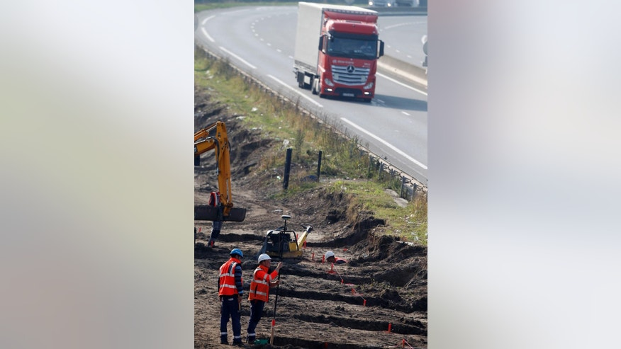 Workers begin construction of a 4-meter- (13-foot) high wall along the roadway leading to the Calais port, outside Calais, northern France, Wednesday, Sept. 21, 2016. The kilometer-long wall being paid for by Britain, is a new barrier to try to keep migrants from crossing the English Channel.(AP Photo/Michel Spingler)