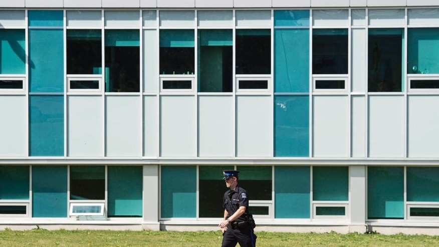 A police officer searches outside the Nova Scotia Community College (NSCC) Institute of Technology Campus in Halifax, Nova Scotia on Wednesday, Sept. 21, 2016. Students were evacuated after police received a threat that bombs were placed at a number of schools. (Darren Calabrese/The Canadian Press via AP)