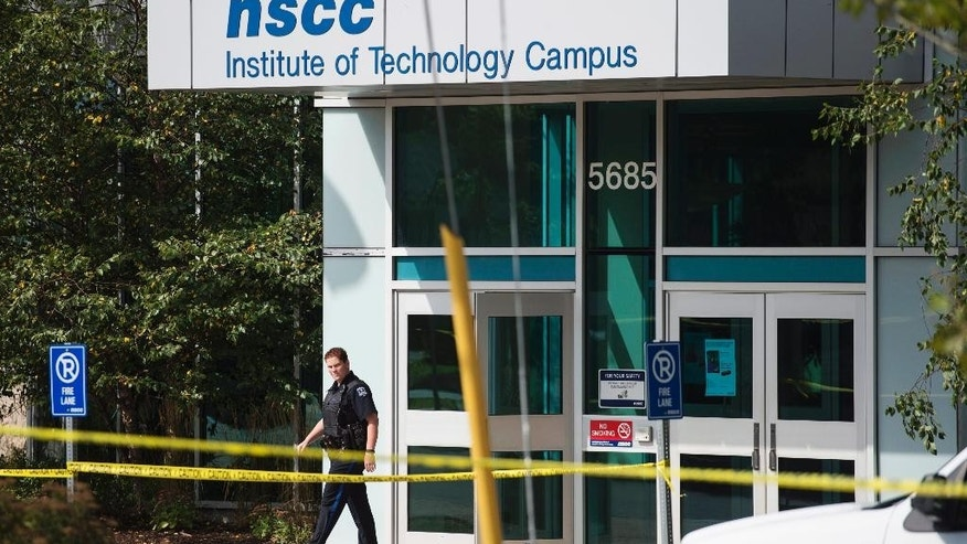 A police officer leaves the Nova Scotia Community College (NSCC) Institute of Technology Campus in Halifax, Nova Scotia on Wednesday, Sept. 21, 2016. Students were evacuated after police received a threat that bombs were placed at a number of schools. (Darren Calabrese/The Canadian Press via AP)