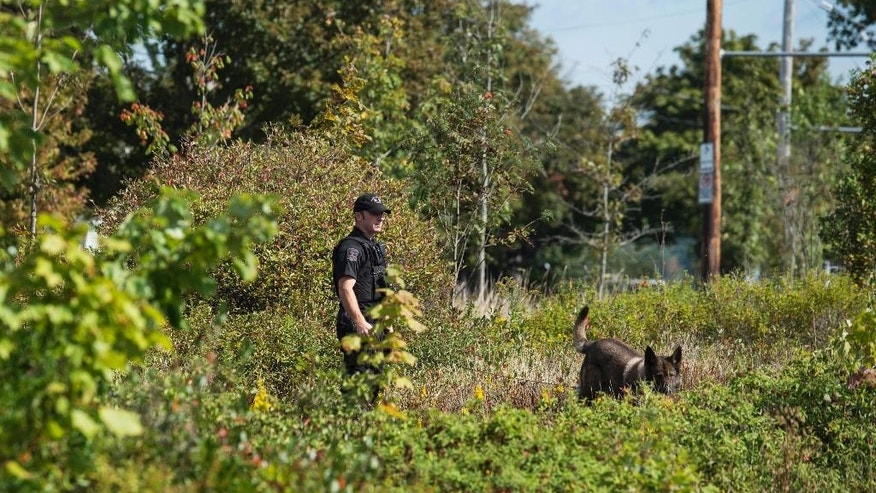 A police officer with the K-9 unit searches an area outside the Nova Scotia Community College Institute of Technology Campus in Halifax, Nova Scotia on Wednesday, Sept. 21, 2016. Students were evacuated after police received a threat that bombs were placed at a number of schools. (Darren Calabrese/The Canadian Press via AP)