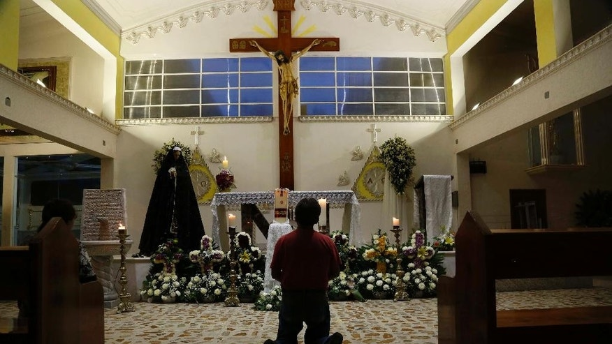 A person prays in Our Lady of Fatima Church in Poza Rica, Veracruz state, Mexico, Tuesday, Sept. 20, 2016. Two of the church's priests were found dead on Monday, and were last seen Sunday. Their bullet-ridden bodies were found on a roadside. (AP Photo/Marco Ugarte)