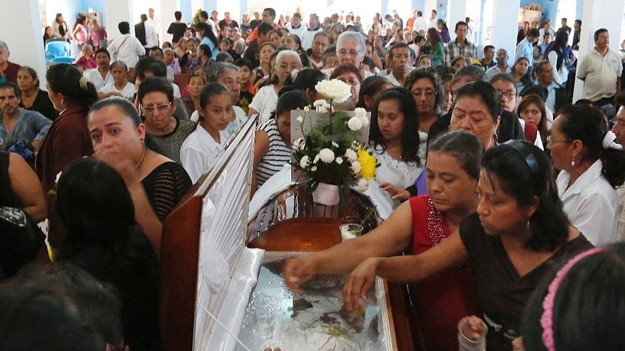 Mourners pay their last respects to slain Rev. Jose Alfredo Suarez de la Cruz at Our Lady of Asuncion Church in Paso Blanco, Veracruz state, Mexico, Wednesday, Sept. 21, 2016. Mourners packed the church for the funeral Mass in memory of the Roman Catholic priest who was murdered along with another cleric in the troubled Gulf coast state of Veracruz. (AP Photo/Marco Ugarte)