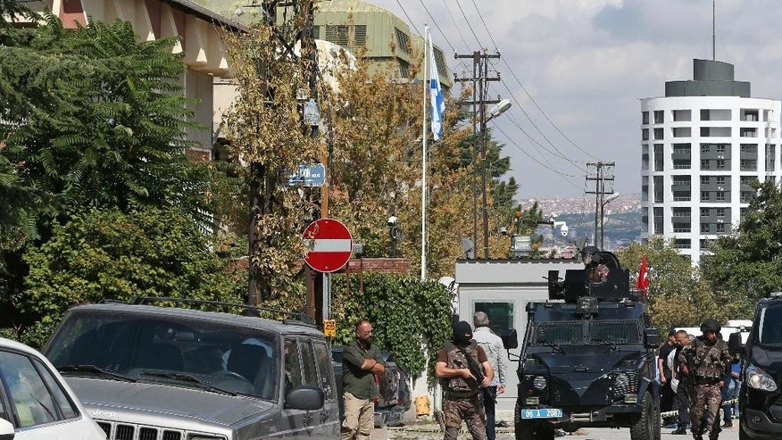 Armed forces near the scene outside the Israeli embassy, left, in Ankara, Turkey where a solo attacker was shot and wounded Wednesday Sept. 21, 2016. (AP Photo/Burhan Ozbilici)