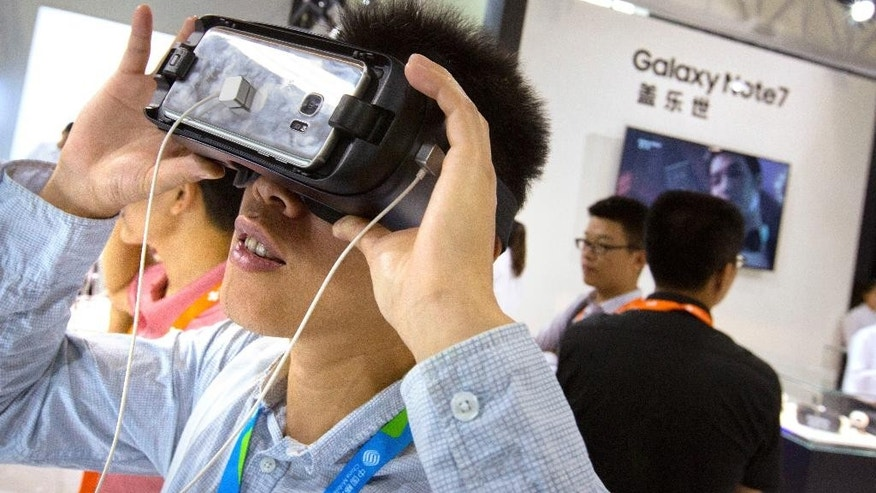 A visitor tries out a Samsung Gear VR headset at a Samsung Electronics display booth during an electronics expo in Beijing, Wednesday, Sept. 21, 2016. Samsung Electronics says its smartphones sold in China don't suffer the same problems as units that caught fire in the United States but Chinese customers complain the company is doing too little to reassure Chinese owners their handsets are safe. (AP Photo/Mark Schiefelbein)