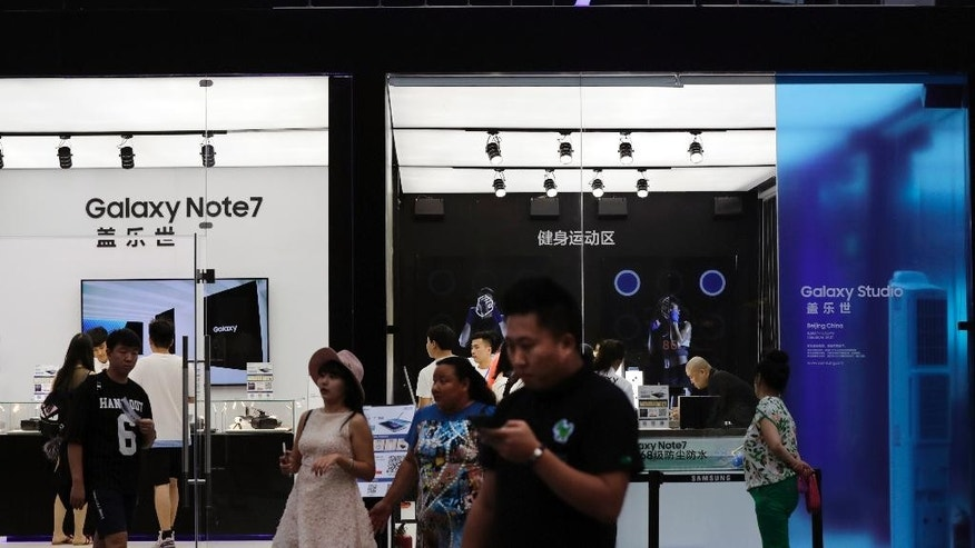 FILE - In this Sept. 1, 2016 file photo, Chinese people visit the Samsung roadshow booth promoting their latest Galaxy Note 7 outside a shopping mall in Beijing. Samsung Electronics says its smartphones sold in China don't suffer the same problems as units that caught fire in the United States but Chinese customers complain its response to the product safety scare ignored them. (AP Photo/Andy Wong, File)