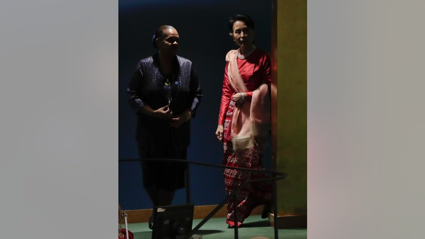 Myanmar leader Aung San Suu Kyi,  right, is escorted to the podium to speak during the 71st session of the United Nations General Assembly, Wednesday, Sept. 21, 2016, at U.N. headquarters. (AP Photo/Julie Jacobson)