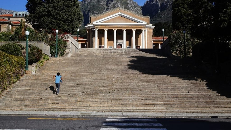 A man runs up stairs at the University of Cape Town, UCT, campus were students gathered during recent protest demanding free education in Cape Town, South Africa, Wednesday, Sept. 21, 2016. Students have staged protests on some other South African campuses. Classes were suspended Wednesday at the University of Cape Town because of security concerns. (AP Photo/Schalk van Zuydam)
