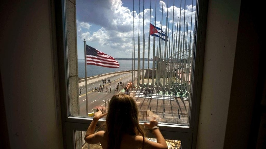 """FILE - In this Aug. 14, 2015 file photo, a girl looks out from the newly opened U.S. Embassy after the U.S. flag raising ceremony in Havana, Cuba, as part of officially restored diplomatic relations. U.S. presidential candidate Donald Trump had been generally supportive of the normalization of relations with Cuba, but on Friday, Sept. 16, 2016 the Republican nominee pledged to reverse Obama's series of executive orders unless Cuba's President Raul Castro meets demands including """"religious and political freedom for the Cuban people and the freeing of political prisoners."""" (AP Photo/Ramon Espinosa, File)"""