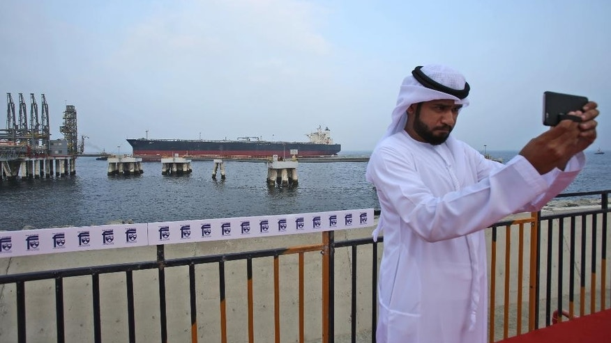 "An Emirati official takes a selfie as an oil tanker approaches the new Jetty during the launch of the new $650 million oil facility in Fujairah, United Arab Emirates, Wednesday, Sept. 21, 2016. The U.A.E has opened its first jetty outside the Persian Gulf that is capable of loading oil onto some of the world's biggest tanker ships. The launch of the facility will make it easier for hulking tanker ships known as ""very large crude carriers"" to load their cargo rather than have it ferried to them out at sea. (AP Photo/Kamran Jebreili)"