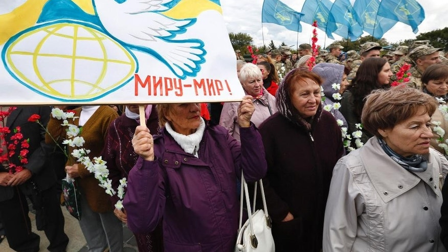 "Ukrainians carry flowers and flags as they take part in the Peace March in Kiev, Ukraine, Sept. 21, 2016, during the International Day of Peace. The placard reading ""Peace to the World"". (AP Photo/Sergey Chuzavkov)"