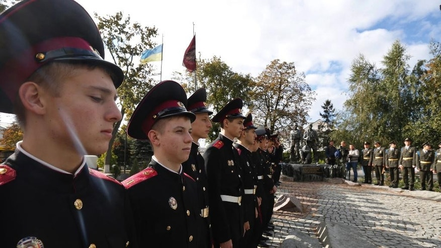 Ukrainian lyceum school students and military cadets stand at a memorial for soldiers killed during the Soviet war in Afghanistan as they take part in the Peace March in Kiev, Ukraine, Sept. 21, 2016, during the International Day of Peace. (AP Photo/Sergey Chuzavkov)