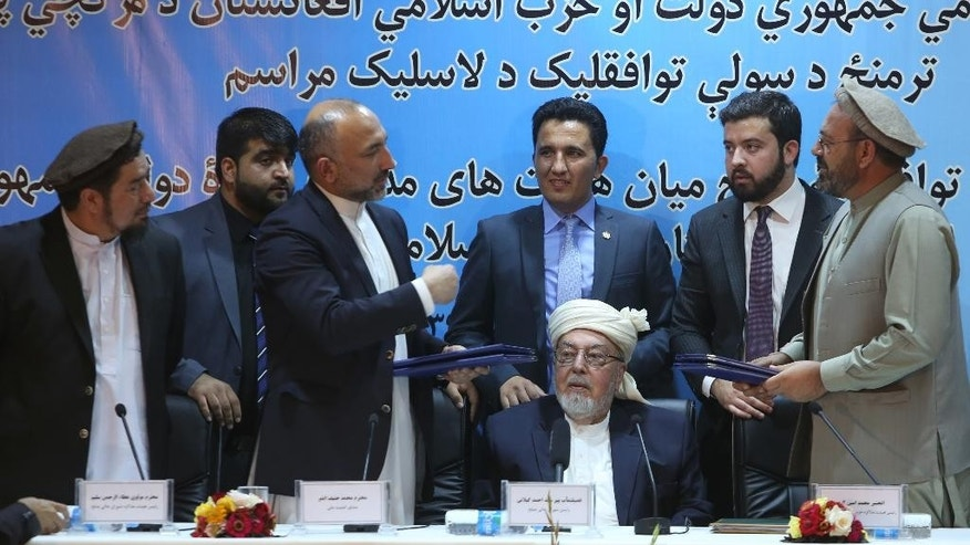 "Amin Karim, representative of Gulbuddin Hekmatyar, right, and Afghanistan national security adviser Mohammad Hanif Atmar, third left, hold their documents after signing a peace deal, in Kabul, Afghanistan, Thursday, Sept. 22, 2016. The Afghan government has signed a draft peace deal with Hizb-i-Islami Gulbuddin, a designated ""global terrorist"" after lengthy negotiations that could pave the way for a similar accord with the Taliban. It grants full political rights to Gulbuddin's Hezb-i-Islami party and obliges the Afghan authorities to work to have it removed from the United Nations' list of foreign terrorist organizations. (AP Photo/Rahmat Gul)"