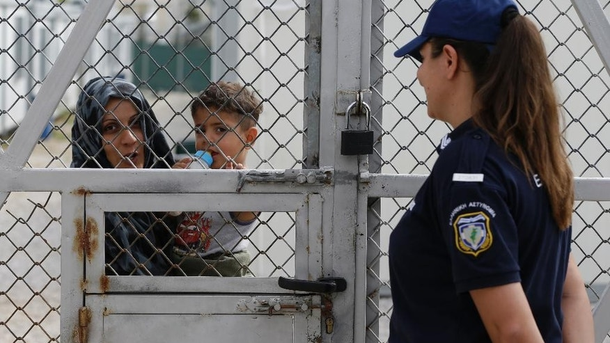 An Iraqi woman holds her baby behind the fence as a policewoman stands guard at Amygdaleza pre-departure center for refugees and migrants who are asking to return home, in Athens, Wednesday, Sept. 21, 2016. The old migrant detention center with capacity for 300 people will be used to temporarily house those who voluntarily return to their countries. More than 60,000 migrants and refugees are stranded in transit in Greece. (AP Photo/Thanassis Stavrakis)