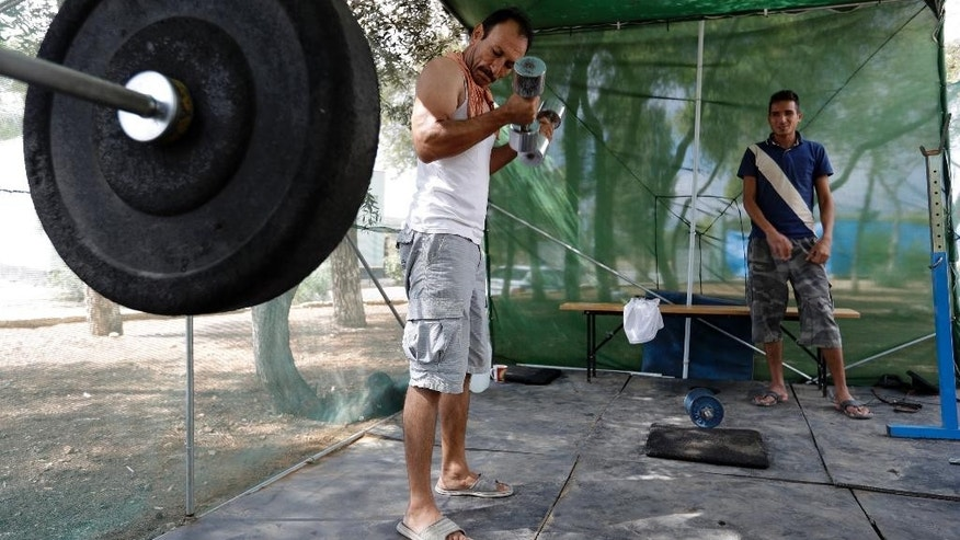 "An Afghan man uses a makeshift gym at a refugee camp in the western Athens' suburb of Schisto, on Thursday, Sept. 22, 2016. Most of the roughly 60,000 refugees and other migrants stranded in Greece are living in ""appalling conditions"" and face ""immense and avoidable suffering,"" rights group Amnesty International said in a report Thursday slamming Europe's response to the refugee crisis. (AP Photo/Thanassis Stavrakis)"