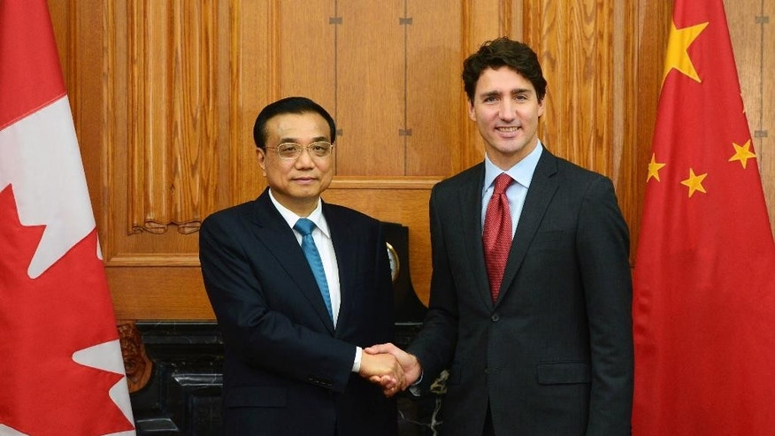 Canadian Prime Minister Justin Trudeau greets Chinese Premier Li Keqiang, left, as holds an expanded meeting in the Cabinet room on Parliament Hill in Ottawa on Thursday, Sept. 22, 2016. (Sean Kilpatrick/The Canadian Press via AP)