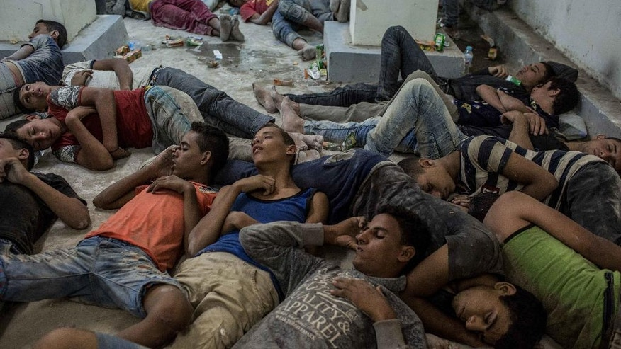 Young Egyptians detained at a police station sleep on the floor in Rosetta, Egypt, after rescued from a boat capsized off the Mediterranean coast near the Egyptian city of Alexandria, Wednesday, Sept. 21, 2016. Egypt's official news agency MENA said the boat was carrying 600 people when it sank near the coast, some 180 kilometers (112 miles) north of the capital, Cairo. (AP Photo/Eman Helal)