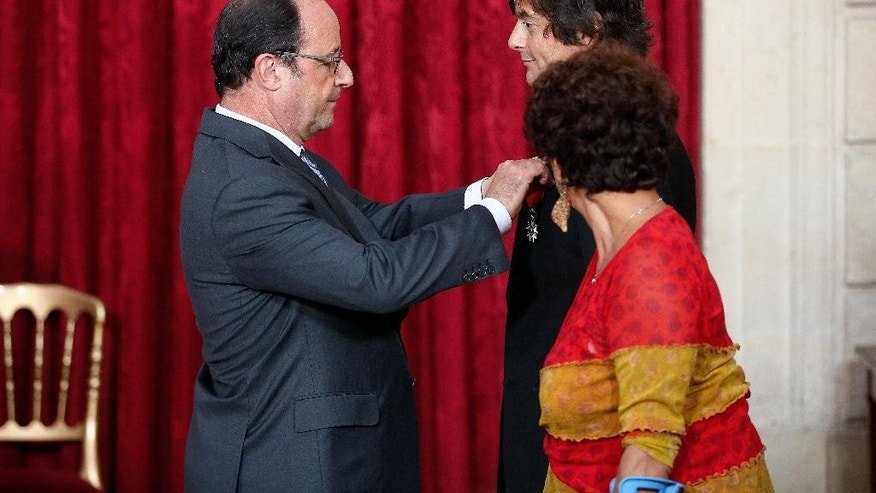 France's President Francois Hollande awards French-American Mark Mooligan with the Legion of Honor by France's President Francois Hollande, at the Elysee Palace, in Paris, Thursday, Sept. 22, 2016. Mooligan, 52, a French-American who was among the heroes who stopped a gunman on a high-speed train in 2015, and was wounded after grabbing his assault rifle. (AP Photo/Thibault Camus, Pool)