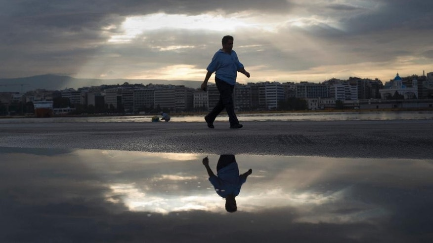 A striking seaman is reflected on a puddle as he walks at the port of Piraeus, near Athens, during the first day of a 48-hour strike by the Panhellenic Seamen's Union (PNO) to protest new austerity measures that government plans, on Thursday, Sept. 22, 2016. Bailout-dependent Greece has agreed to carry out new austerity measures and reforms to secure vital rescue loans from its European creditors. (AP Photo/Petros Giannakouris)