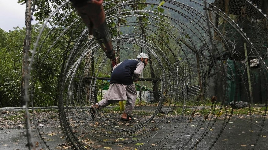 A Kashmiri man ducks to cross an iron barricade with coils of razor wire near a military base at Braripora, near the de facto border dividing Kashmir between India and Pakistan, in Indian controlled Kashmir, Wednesday, Sept. 21, 2016. Indian soldiers on Wednesday searched areas near the de facto border where two gunbattles with suspected rebels raged for half a day, the Indian army said. The clashes came three days after suspected rebels killed more than 15 Indian soldiers in an audacious attack on a crucial military base in Uri. The militants also were killed. (AP Photo/Mukhtar Khan)