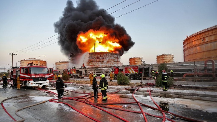 """In this photo released by the semi-official Iranian Isna News Agency, and taken on July 4, 2016, firefighters try to extinguish a blaze at the Bou Ali Sina Petrochemical Complex at the Imam Khomeini port, southwestern Iran. A series of fires at Iranian petrochemical plants and facilities have raised suspicions about hacking potentially playing a role in the blazes. Iran officially insists the six known blazes this summer weren't the result of a cyberattack. However, authorities themselves saying that """"viruses had contaminated"""" equipment at several of the affected complexes. (Borna Ghasemi/ISNA via AP)"""