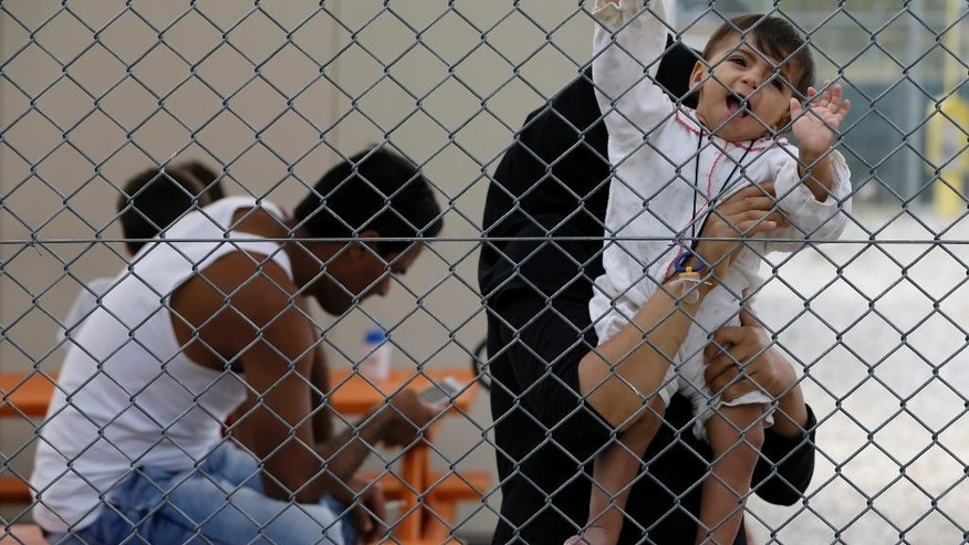 A baby holds the fence at Amygdaleza pre-departure center for refugees and migrants who are asking to return home, in Athens, Wednesday, Sept. 21, 2016. The old migrant detention center with capacity for 300 people will be used to temporarily house those who voluntarily return to their countries. More than 60,000 migrants and refugees are stranded in transit in Greece. (AP Photo/Thanassis Stavrakis)