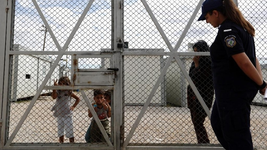 Children from Iraq stand behind the fence as a policewoman stands guard at Amygdaleza pre-departure center for refugees and migrants who are asking to return home, in Athens, Wednesday, Sept. 21, 2016. The old migrant detention center with capacity for 300 people will be used to temporarily house those who voluntarily return to their countries. More than 60,000 migrants and refugees are stranded in transit in Greece. (AP Photo/Thanassis Stavrakis)