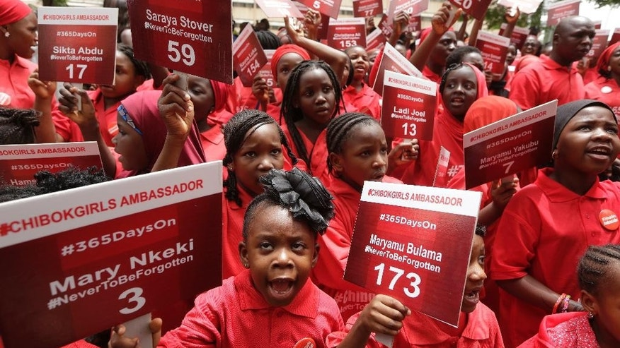 "FILE- In this Tuesday, April. 14, 2015 file photo, young girls known as Chibok Ambassadors, carry placards bearing the names of the girls kidnapped from the government secondary school in Chibok, two years ago, during a demonstration, in Abuja, Nigeria. Nigerian President Muhammadu Buhari is inviting the United Nations to help negotiations to swap the kidnapped schoolgirls from Chibok for detained leaders of the Boko Haram Islamic extremist group. A government statement said Buhari's offer is a ""show of commitment"" made to U.N. Secretary General Ban Ki-moon Wednesday Sept. 21, 2016, on the sidelines of the U.N. General Assembly in New York. AP Photo/Sunday Alamba File)"