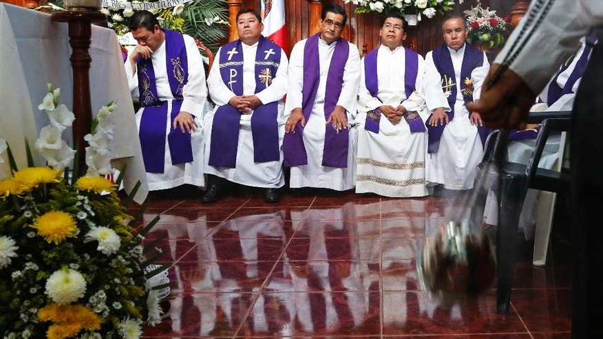 Priests attend the funeral Mass for slain Rev. Jose Alfredo Suarez de la Cruz at Our Lady of Asuncion Church in Paso Blanco, Veracruz state, Mexico, Wednesday, Sept. 21, 2016. Mourners packed the church for the funeral Mass in memory of the Roman Catholic priest who was murdered along with another cleric in the troubled Gulf coast state of Veracruz. (AP Photo/Marco Ugarte)