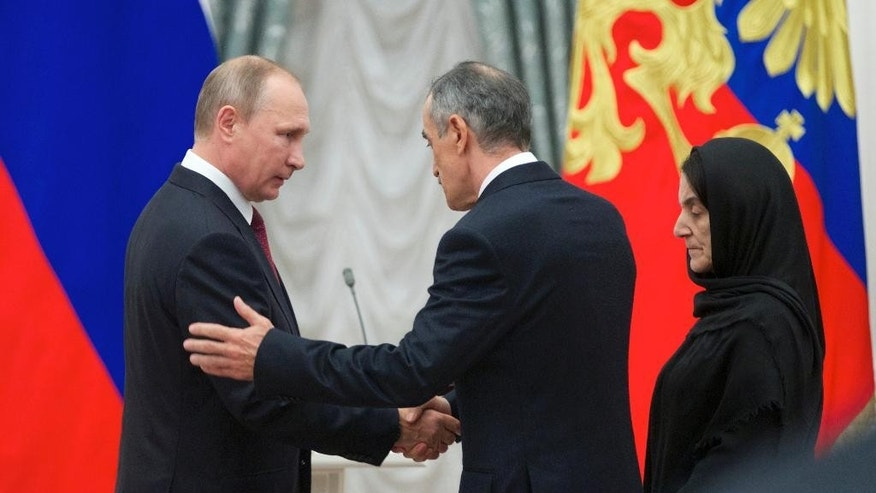 "Russian President Vladimir Putin, left, shakes hands with Nurbagand Nurbagandov, as Kumsiyat Nurbagandova stands at right, during an awarding ceremony in Moscow's Kremlin, Russia, on Thursday, Sept. 22, 2016. They are parents of police officer Magomed Nurbagandov, who was killed by militants in Russia's volatile North Caucasus province of Dagestan. Security services tracked down the militants who killed Nurbagandov and found a video, in which the captors demanded that Nurbagandov urge his colleagues to resign from the police and he defied them, saying: ""Keep on working, brothers!"" before being killed. (AP Photo/Ivan Sekretarev, pool)"