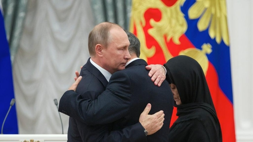 "Russian President Vladimir Putin, left, embraces Nurbagand Nurbagandov, as Kumsiyat Nurbagandova stands at right, during an awarding ceremony in Moscow's Kremlin, Russia, on Thursday, Sept. 22, 2016. They are parents of police officer Magomed Nurbagandov, who was killed by militants in Russia's volatile North Caucasus province of Dagestan. Security services tracked down the militants who killed Nurbagandov and found a video, in which the captors demanded that Nurbagandov urge his colleagues to resign from the police and he defied them, saying: ""Keep on working, brothers!"" before being killed. (AP Photo/Ivan Sekretarev, pool)"