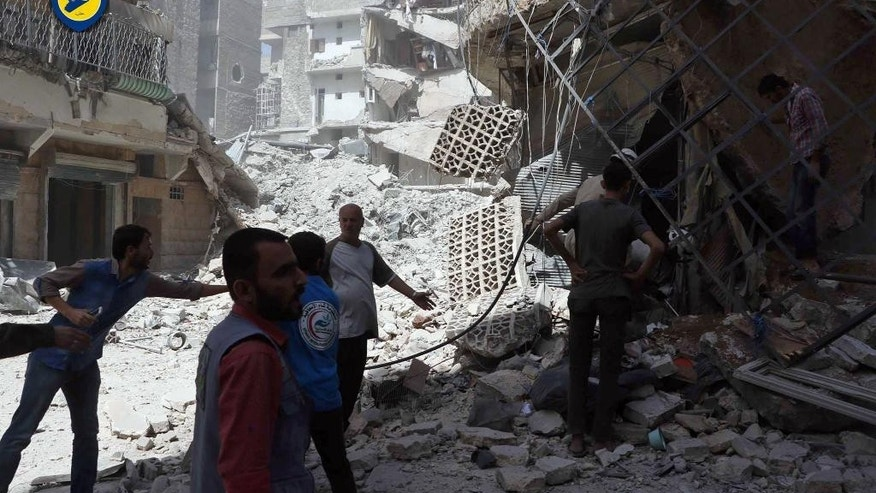 In this photo provided by the Syrian Civil Defense White Helmets, men stand amid rubble after airstrikes in al-Mashhad neighborhood in the rebel-held part of eastern Aleppo, Syria, Wednesday Sept. 21, 2016. Ibrahim Alhaj, a member of the volunteer first responders known as the Syria Civil Defense, said 24 people were killed in a series of bombings in several parts of the besieged city Aleppo on Wednesday.  (Syrian Civil Defense White Helmets via AP)