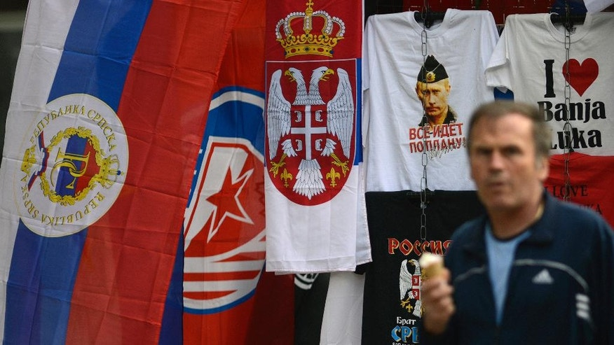 In this photo taken on Wednesday, Sept. 21, 2016. Bosnian man passes by flags of Bosnia's Serb mini state Republic of Srpska and t-shirt with photos of Russian President Vladimir Putin in the Bosnian town of Banja Luka, 240 kms (150 miles) northwest of the Bosnian capital of Sarajevo. Bosnia's Serb mini-state is holding a referendum this weekend that has turned into a proxy political battle between the West and Russia, stoking ethnic tensions and triggering fears of new clashes more than 20 years after the end of the Balkans War. Sunday's vote asks residents of Republika Srpska whether to maintain a national holiday on Jan. 9, despite a ruling of Bosnia's constitutional court that the date discriminates against non-Serbs. (AP Photo/Radivoje Pavicic)
