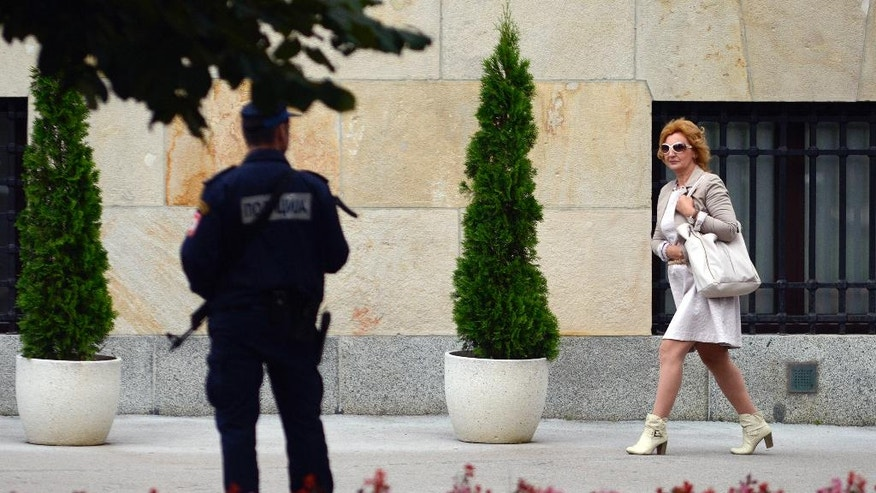 In this photo taken on Wednesday, Sep. 21, 2016, a Bosnian woman passes by armed policemen guarding government building in the Bosnian town of Banja Luka, 240 kms (150 miles) northwest of the Bosnian capital of Sarajevo , Bosnia. Bosnia's Serb mini-state is holding a referendum this weekend that has turned into a proxy political battle between the West and Russia, stoking ethnic tensions and triggering fears of new clashes more than 20 years after the end of the Balkans War. Sunday's vote asks residents of Republika Srpska whether to maintain a national holiday on Jan. 9, despite a ruling of Bosnia's constitutional court that the date discriminates against non-Serbs. (AP Photo/Radivoje Pavicic)