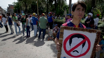 "A young man holds a poster with a black and white stencil depicting Venezuela's President Nicolas with a no symbol and the message; ""Get out Maduro!""  during a protest against Maduro, in Merida, Venezuela, Wednesday, Sept. 7, 2016. Venezuelans are marching in cities across the country Wednesday to demand authorities allow a recall referendum against Maduro to go forward this year. In the college town of Merida some 400 opponents of Maduro unfurled a giant Venezuelan flag and held up signs calling for his removal. (AP Photo/Fernando Llano)"